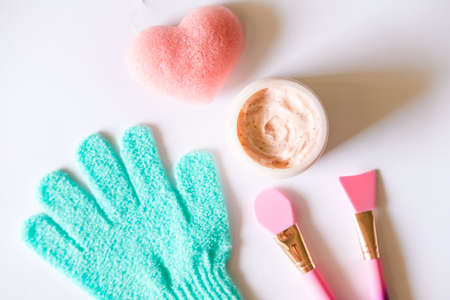 Pink strawberry scrub, silicon brushes, green exfoliating glove and heart shaped sponge on white background. Skin care beauty concept. 版權商用圖片