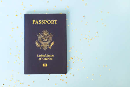 American passport and star shaped glitters on pastel blue background. Archivio Fotografico