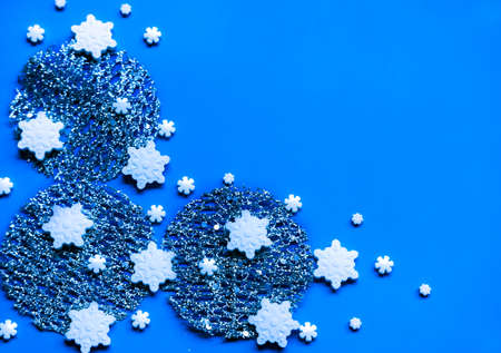 Silver decor, snowflake sprinkles and shiny star shaped glitters on blue background. Winter holidays concept.