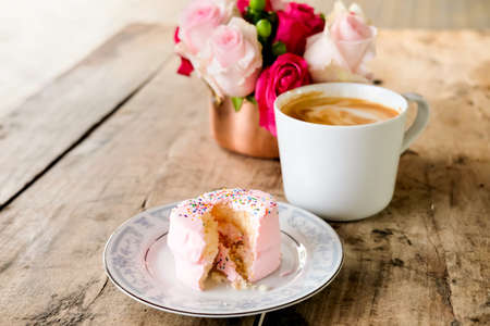 White cup of coffee latte, vanilla cake and pink roses on wooden table. Lifestyle concept.