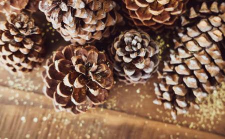 Weihnachten festlich gestaltete Tannenzapfen und goldener Glitzerhintergrund. Winterferien-Konzept. Standard-Bild