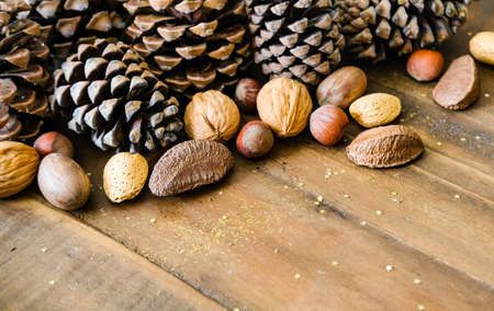 Christmas festive styled pine cones, nut mix and golden glitters background. Winter holidays concept.