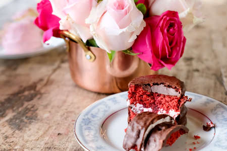 Red velvet cake and pink roses on wooden table. Lifestyle concept.  写真素材