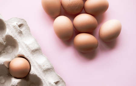 Brown eggs in biodegradable carton on pastel pink background. Holiday concept. Minimal composition.