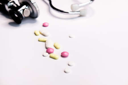 Professional silver black Stethoscope and colorful pills on white background.  Stockfoto