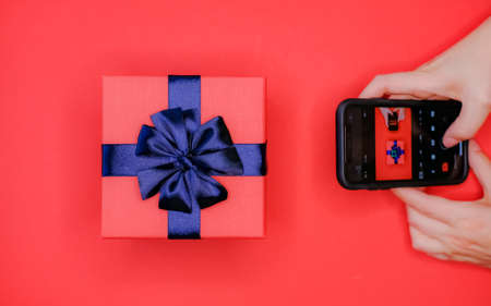 Black cellphone in womans hands and gift box with blue bow on vivid red background. Flat lay lifestyle concept. Taking picture on camera with mobile phone. 스톡 콘텐츠