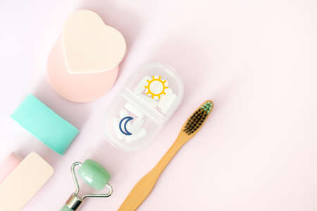 Green jade face roller, natural bamboo toothbrush, pill case and sponges on pastel pink background. Flat lay style. Modern self care beauty concept. 写真素材