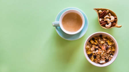 Cup of coffee espresso, nuts mix, and muesli on mint green background. Heathy breakfast concept.