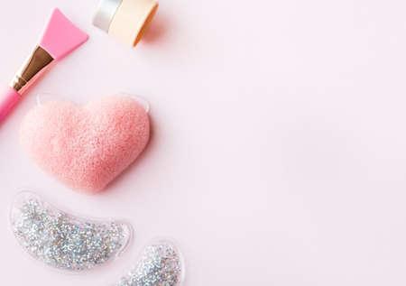 Pink silicon brush, sponge, moisturizer and under eye pad on pastel background. Skin care beauty concept. 免版税图像