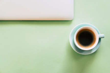 Cap of coffee and silver laptop on mint green background. Mockup. Office concept.