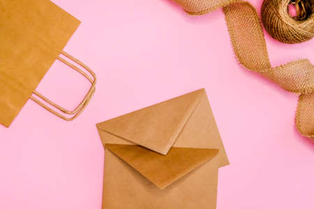 Kraft paper envelops, bag and burlap ribbon on pink background. Festive trendy concept, natural flat lay design.