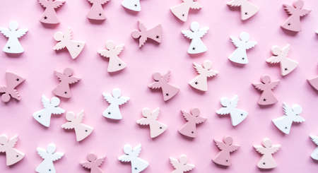 White and pink mini wooden angels pattern on pastel background. Festive trendy concept.