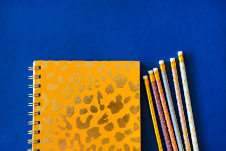 Pink notebook and cute golden pencils on trendy dark blue background. Flat lay minimalism style. Stock Photo