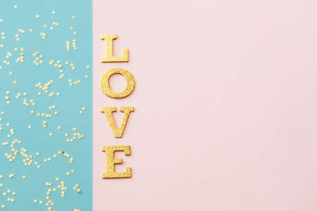 Golden shiny word Love and star shaped glitters on blue pink background. Valentines day concept.