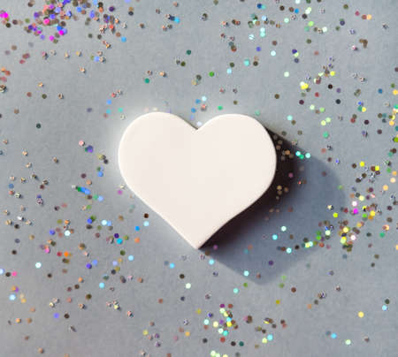 White heart and hologram glitters on gray background. Valentines day concept. Stock Photo