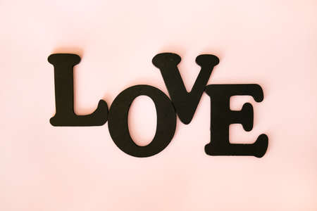Black word Love on coral pink pastel background. Valentines day concept background.