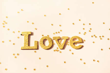 Golden shiny word Love and star shaped glitters on pastel yellow background. Valentines day concept background.