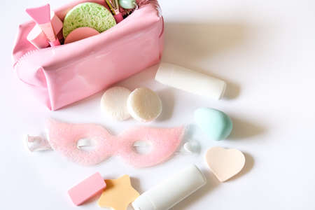 Pink cosmetic bag, beauty products, eye mask, mini soaps, silicon brushes, jade roller and different shapes sponges on white background. Skin care concept. Banque d'images