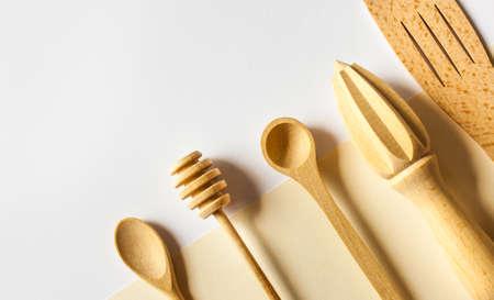 Handmade wooden cutlery on beige white background, wood kitchen tools.