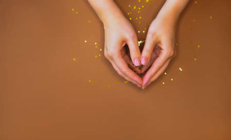 Womans hand and golden glitters on warm brown background. Reklamní fotografie