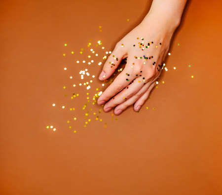 Woman's hand and golden glitters on warm brown background.