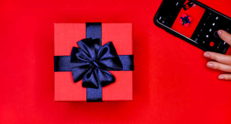 Black cellphone in womans hands and gift box with blue bow on vivid red background. Flat lay lifestyle concept. Taking picture on camera with mobile phone. Stock Photo