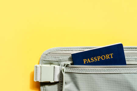 Travel concept. Passport and organizer belt wallet flat lay on yellow background. 版權商用圖片