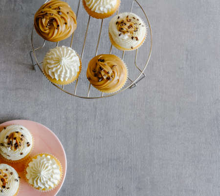 Vanilla and caramel cupcakes with cream cheese frosting on gray background. Sweet food concept.