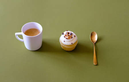 Vanilla cupcakes with cream cheese frosting and white cup of coffee on green background. Sweet food concept.