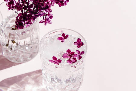 Beautiful vivid lilac flowers in crystal glass on pink background.