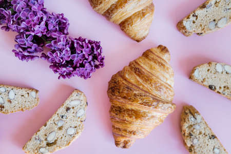 Freshly baked classic croissants, almond biscottis and lilac flowers on pink background. Breakfast food concept.