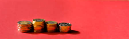 Stacks of coins over red background banner. Saving money concept. 免版税图像