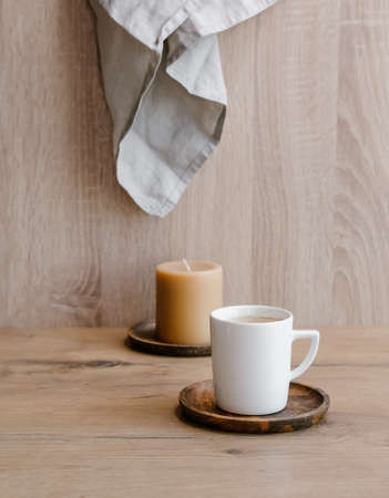 White cup of coffee and caramel candle on wooden background. 免版税图像