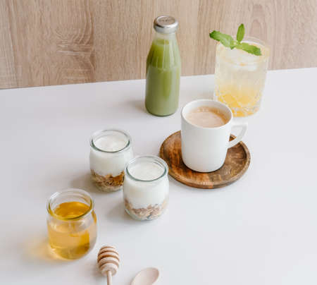Healthy breakfast set with coffee, homemade yogurts with granola, honey or agave syrup and green juice.