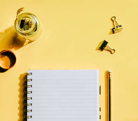 Notebook and golden pencil and paper clips on yellow background. Back to school concept. 免版税图像