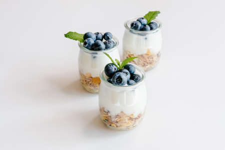 Homemade natural yogurt with granola and blueberries in glass jars on white background. Healthy breakfast set.