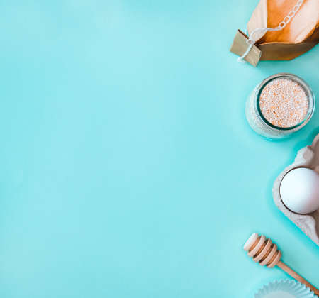 Baking ingredients, flour, milk and eggs on pastel turquoise background. Food flat lay concept. 免版税图像