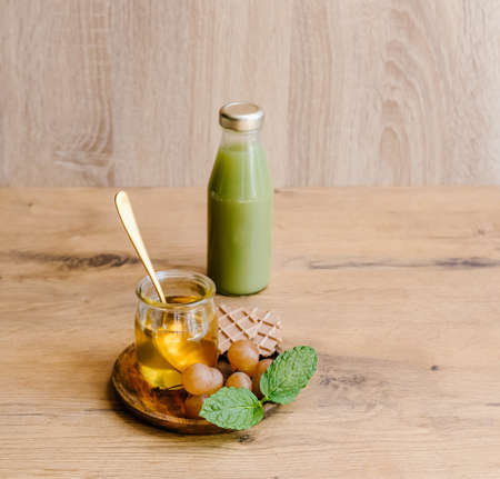Healthy snack set with muscat grapes, honey and green juice on wooden background.