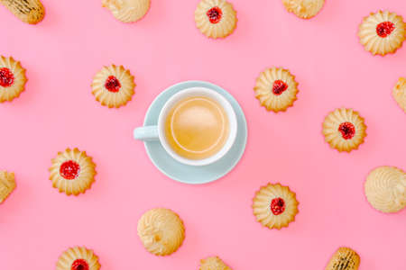 Coffee and cookies with cranberries jam and almonds on pink background. Holidays food concept.
