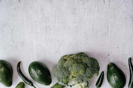 Green fresh veggies frame monochrome background, top view, healthy food concept. 免版税图像