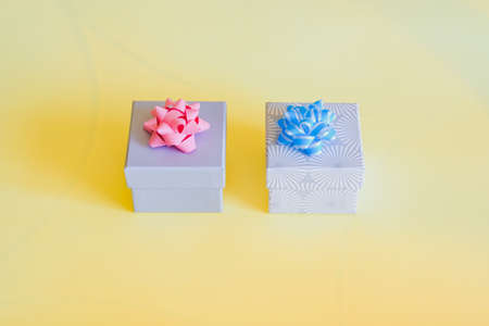 Colorful gift boxes and bows on sunny yellow background. Festive happy holidays design. 免版税图像