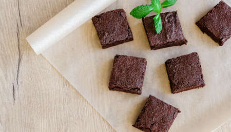 Freshly baked classic fudge brownie on parchment brown paper and wooden table background. Homemade sweet food. 免版税图像