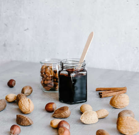 Homemade dark chocolate sauce in glass jars and different nuts, cinnamon sticks and silver whisk on gray marble background.