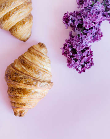 Freshly baked classic croissants and lilac flowers on pink background. Breakfast food concept. 免版税图像