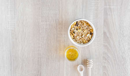Healthy breakfast set with different nuts, coffee, honey or agave syrup and fruits.