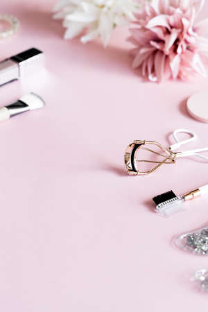 Cosmetic products: lip gloss, lipstick, jade roller, brushes, patches and eyelash curler on pink background. Beauty and makeup concept.