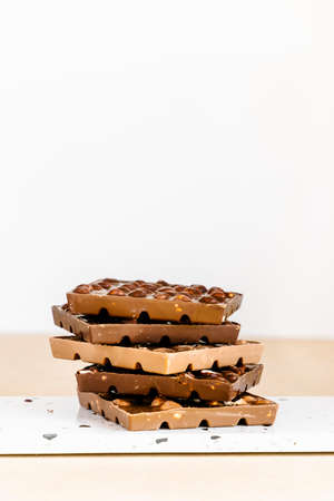 Stack of milk and dark chocolate with hazelnuts and macadamia nuts on white background. 免版税图像