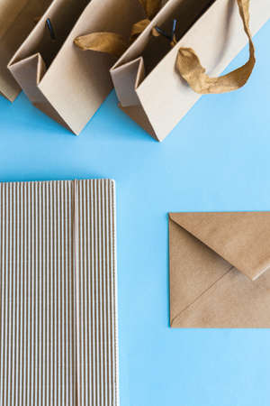 Zero waste concept, kraft brown paper bags and envelope on blue background.