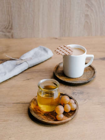 Healthy snack set with muscat grapes, honey and coffee with waffles on wooden background.
