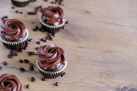 Dark chocolate coffee cupcakes on wooden brown table background. Sweet food concept.